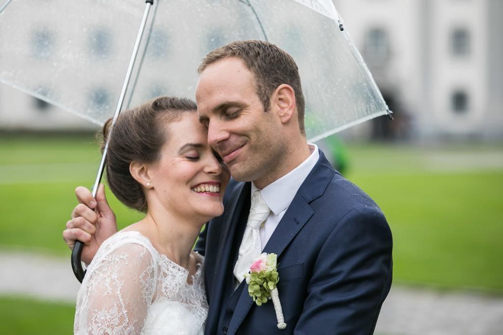 Brautpaar kuschelt und dem Regenschirm.