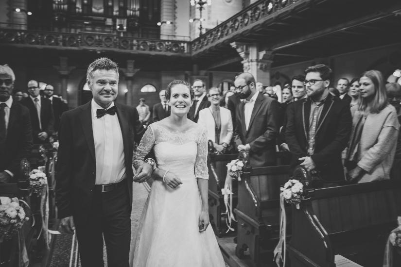 Braut wird von Vater in die Kirche begleitet.
