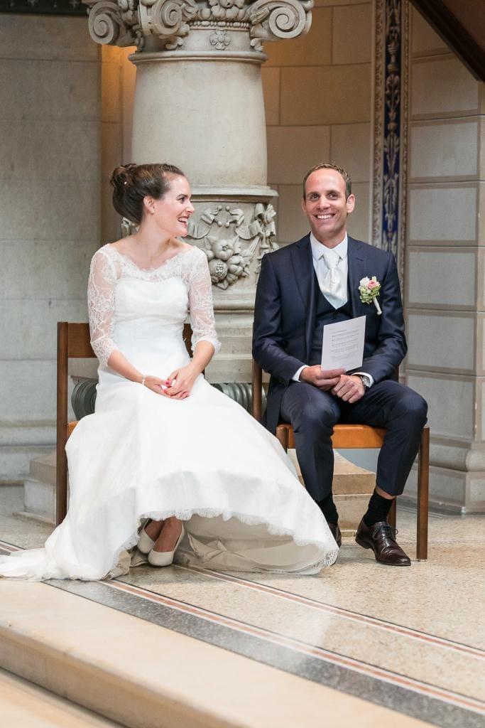 Lachendes Brautpaar sitzt in der Kirche.