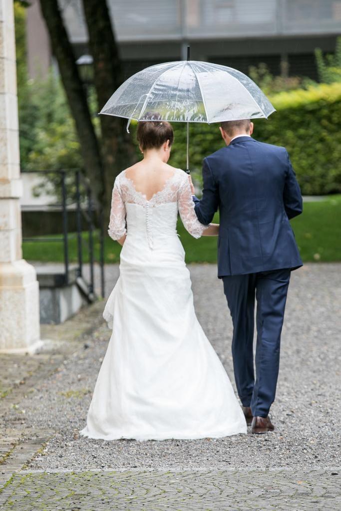 Brautpaar von Hinten, laufen mit einem Regenschirm davon.