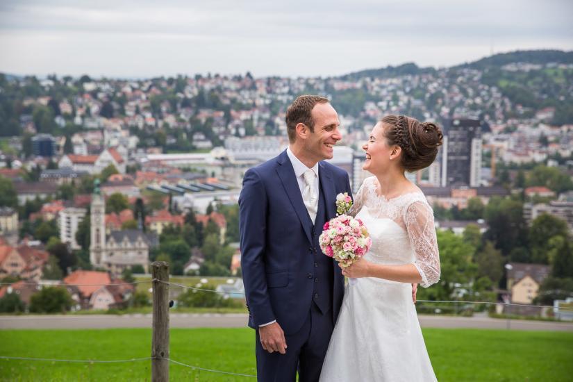 lachendes Brautpärchen mit Brautstrauss.