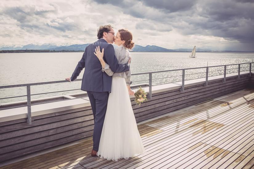 küssendes Brautpaar am Bodensee, im Hintergrund fährt ein Segelboot.