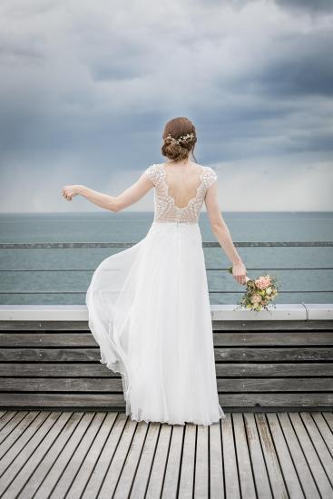 Braut von hinten am Wasser.