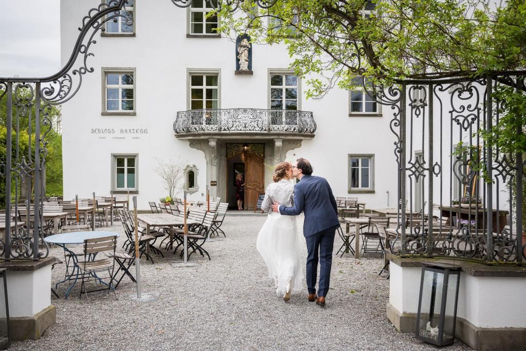 Brautpaar läuft küssend ins Schloss