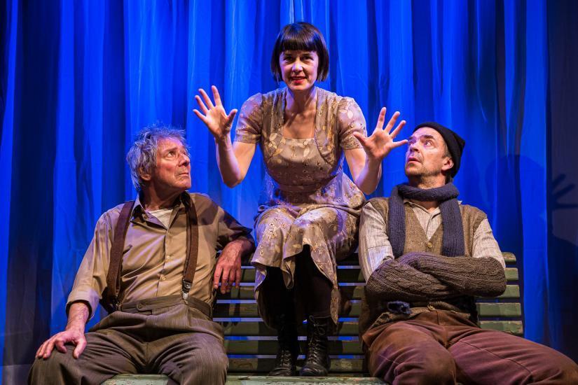 drei Schauspieler sitzen auf einer Sitzbank